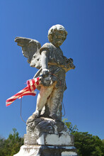 Old Worn Angel Statue With Tattered Flag And Blue Sky