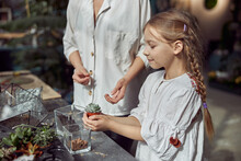 Caucasian Confident Happy Florist Is Working With Her Young Daughter And Making Composition From Glass Stones And Plants In Botanic Shop