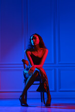 African American Woman In Dress, Fishnet Tights Sits On Chair With Hand Bag Under Neon Lights