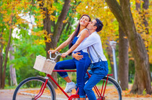 Teen Couple With Retro Bike Kissing In The Park In Autumn Time