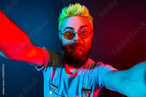 Extremely crazy bearded hipster man blogger with green hair wears denim overalls, showing tongue out, having fun posing on selfie camera, live streaming фототапет