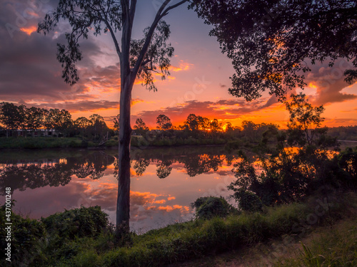 Fotografia Spectacular Riverside Sunset with Cloud Reflections