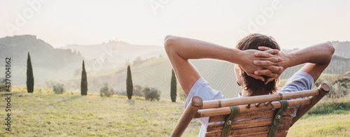 Fotografiet Young man looking at the valley in Tuscany, Italy, relaxation, vacations, lifestyle, summer fun, have a good day, enjoying life concept