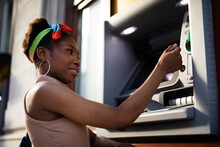 Beautiful African Womn Using ATM Machine. Attractive Young Woman Withdrawing Money From Credit Card At ATM.