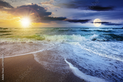 day and night time change concept above sea tide on a cloudy twilight. green waves crashing golden sandy beach with sun and moon above the horizon. storm weather approaching. summer holiday concept #437008000
