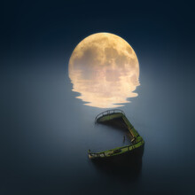 Broken Ship On Dreamy Nightscape With Full Moon And Water Reflections