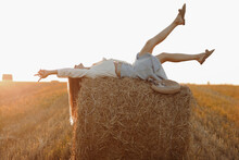 Young Woman With Long Hair, Wearing Jeans Skirt, Light Shirt Is Lying On Straw Bale In Field In Summer On Sunset. Female Portrait In Natural Rural Scene. Environmental Eco Tourism Concept.