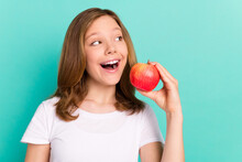 Photo Portrait Schoolgirl Cheerful Eating Red Apple Looking Copyspace Isolated Bright Turquoise Color Background