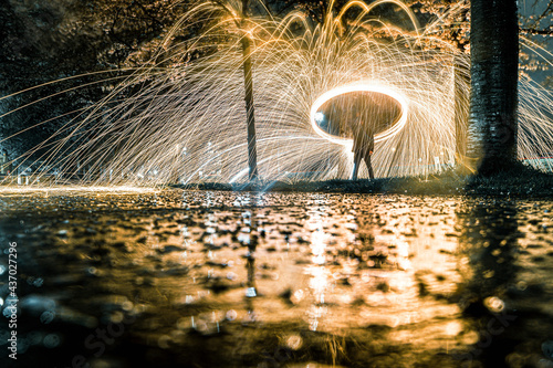 Valokuvatapetti Sparkling fireworks in city park with blooming cherry blossom avenue