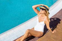 Happy Woman Sitting On Poolside And Sunbathing