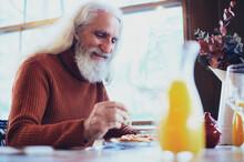 Elderly Man Eating Tomato Toast In Restaurant