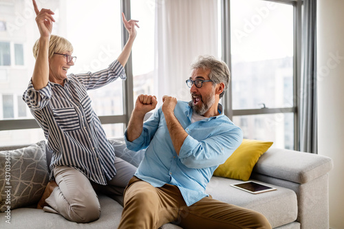 Excited mature couple having fun at home Fotobehang