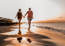Couple Strolling On Sandy Beach At Sunset
