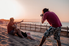 Male Photographer Taking Photos Of Couple Resting On Beach