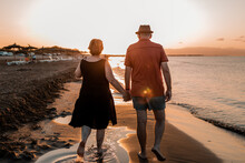 Anonymous Couple Strolling On Sandy Beach At Sunset