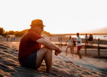 Adult Man Sitting On Sandy Beach At Sunset