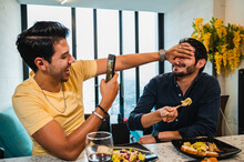 Happy Gay Taking Photo Of Ethnic Boyfriend On Smartphone Indoors