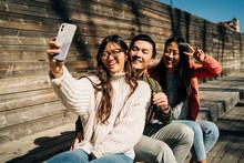 Joyful Young Ethnic Millennials Taking Selfie Sitting On Bench