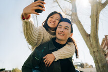 Loving Young Asian Couple Taking Selfie While Cuddling In Park