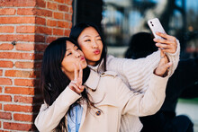Happy Young Asian Ladies Pouting Lips While Taking Selfie On Street