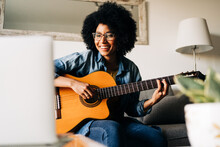 Positive Black Woman Playing Guitar At Home
