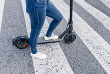 Anonymous Female Riding Electric Scooter On Crosswalk
