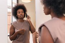 Self Assured Young Black Woman Brushing Afro Hair Near Mirror
