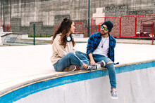 Cheerful Friends In Stylish Casual Outfits Talking On Parapet