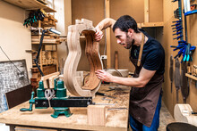 Luthier Building Guitar At Table In Workshop