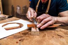 Crop Craftsman Cutting Wooden Piece With Saw In Workshop