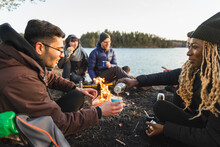 Black Woman Pouring Tea From Thermos Sitting Near Bonfire