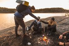 Diverse Friends Having Fist Bump Near Campfire