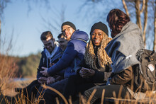 Joyful Diverse Friends Communicating In Forest While Resting During Trekking