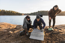 Happy Campers Putting Folding Mat On Lake Coast