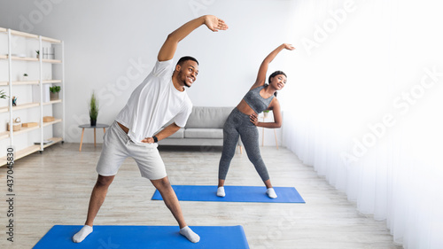 Foto Athletic black couple bending aside, doing exercises at home, banner design with