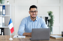 Online Foreign Languages Tutoring. Cheerful Arab Male Teacher Giving French Class, Communicating On Laptop From Home