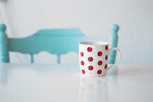 A Large White Cup Of Coffee Or Tea With Red Dots Stands On A White Table. A Navy Blue Greek-style Chair Stands Next To The Table. Illuminated Kitchen