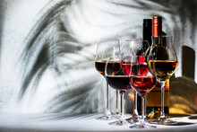 Wines Assortment. Red, White, Rose Wine In Wineglasses On Gray Background. Wine Tasting Concept. Hard Sunlight And Shadows From Foliage