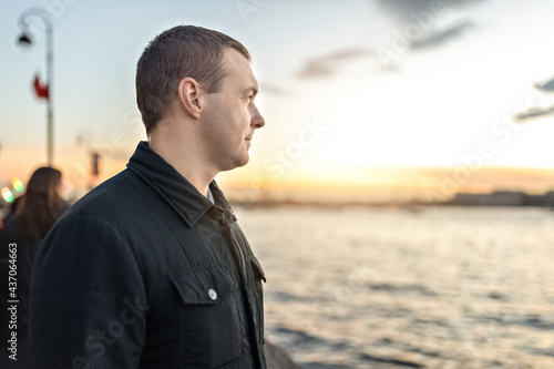 Fotografia Portrait of a young man watching the sunset on the embankment of the river in th