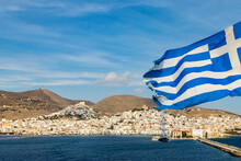 Greek Flag Swaying On The Background Of The Syros Island