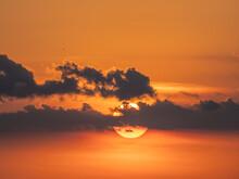 Sun Behind Small Clouds In Orange Sky Near Sunse