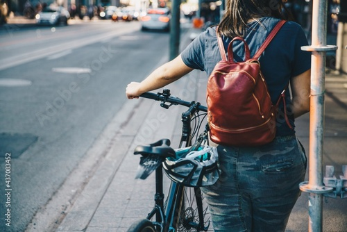 A person with a backpack pushing her bike through the city sidewalks.