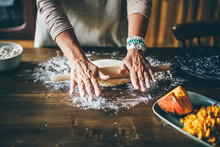 Aged Woman Prepare Pastry Dough Rolling Out Round Piece With Wooden Pin Standing At Kitchen Table In Country Style Interior.