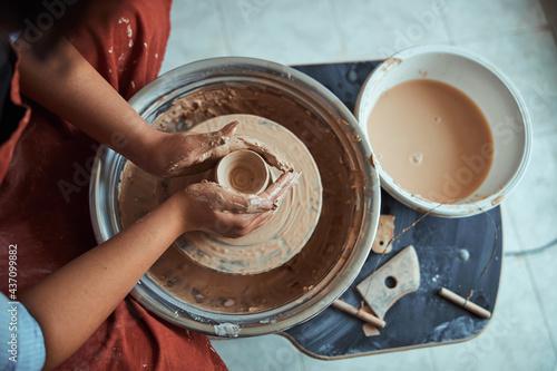 Fotografiet Female potter hands throwing earthenware pot on pottery wheel