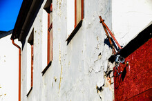 A Surveillance Camera On A Red And White Decayed Wall With Peeling Paint And Masonry