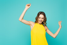 Cheerful Woman In Yellow Dress Dancing Isolated On Blue