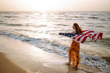 Young Woman With American Flag On The Beach At Sunset. 4th Of July. Independence Day. Patriotic Holiday.