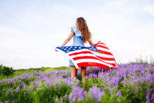 Young Woman With American Flag On Blooming Meadow. 4th Of July. Independence Day. Patriotic Holiday. USA Flag Fluttering In The Wind.