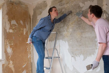 Young Couple Has An Argue About New Design In Unfinished Living Room During Home Renovations.