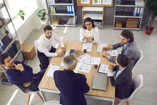 High Angle Of Group Of Young Male And Female Employees Listening To Director Sitting Around Office Table In Corporate Meeting. White-haired Senior Man Standing By The Table Talking To Team Of Workers